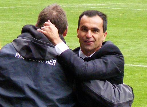Roberto Martinez is embraced by a photographer